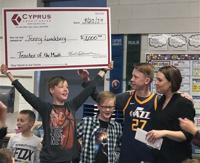 Student holding large check with teacher